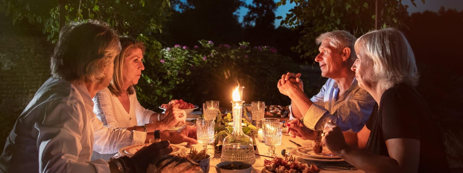 Amis qui discutent autour d'un repas au coucher de soleil