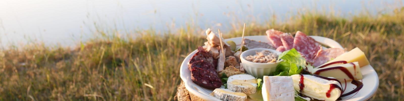 Assiette de fromage et de charcuterie au bord d'un point d'eau