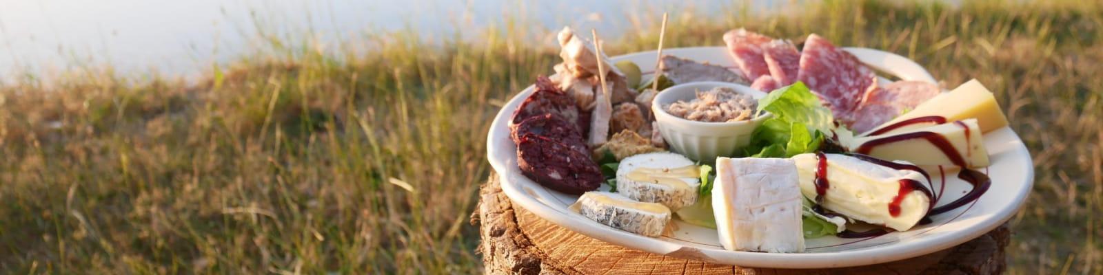 Assiette de charcuterie et de fromage au bord d'un étang