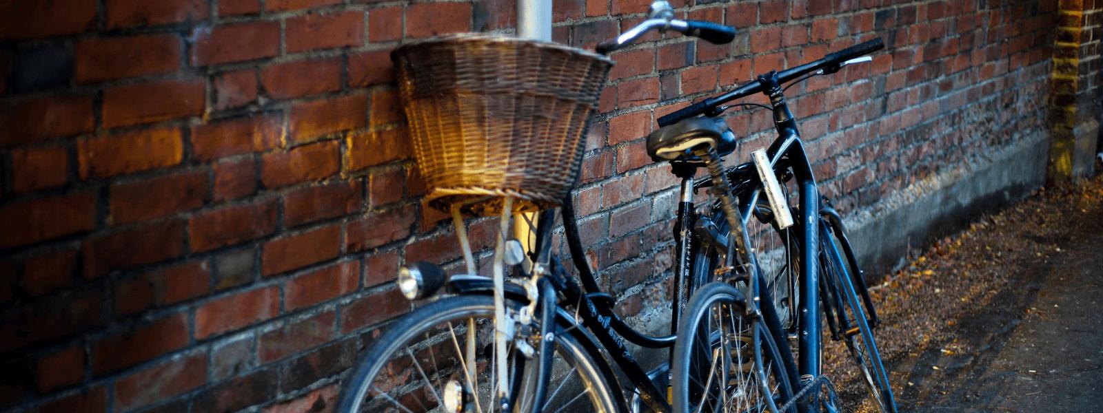2 vélos posées sur les murs d'une maison de briques